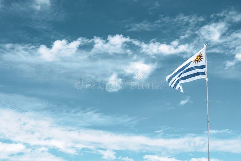 乌拉圭在多云天空的旗子波动 免版税库存图片