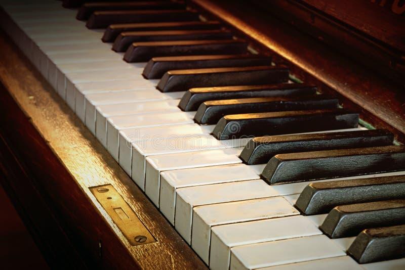 从乌木和象牙,被定调子的温暖的颜色的古色古香的琴键 免版税库存照片