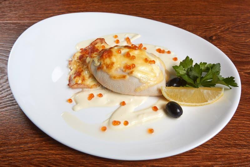 乌贼充塞用乳酪和被烘烤的比目鱼,装饰用白汁和红色鱼子酱,在切片柠檬旁边,香菜 免版税库存照片