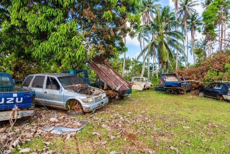乌韦阿岛,瓦利斯和富图纳群岛 汽车坟园,汽车公墓围场,被放弃的汽车废品旧货栈在一个遥远的海岛上的棕榈树下 免版税库存图片