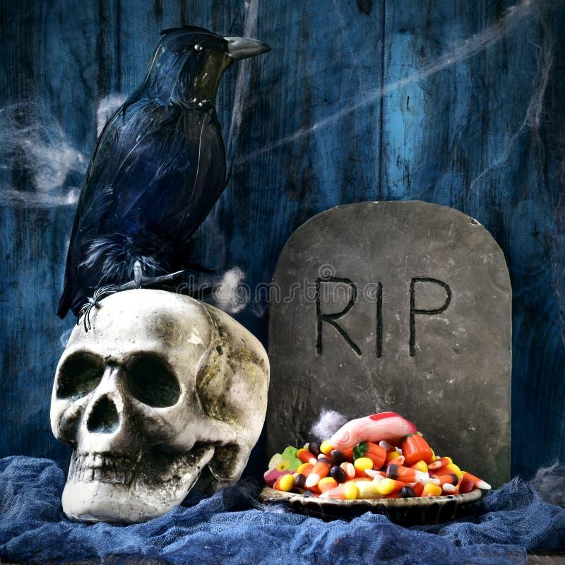 乌鸦、头骨、墓碑和万圣夜糖果 库存照片