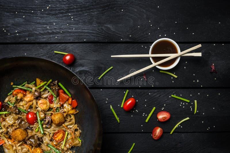 乌龙面混乱油炸物面条用海鲜和菜在铁锅平底锅在黑木背景 筷子和调味汁 图库摄影