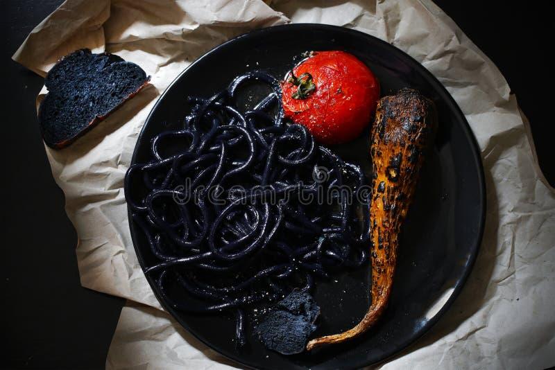 黑乌龙面面条、面团与乌贼墨水,蕃茄和红萝卜 免版税库存图片