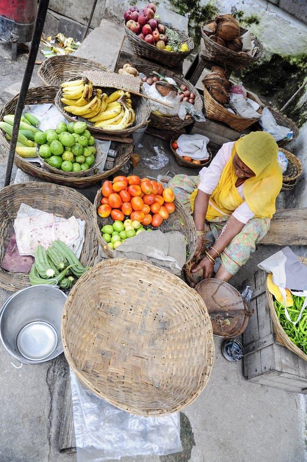 乌代浦,印度, 2010年9月14日:卖蔬菜和水果在一个地方街市上的老妇人在乌代浦 库存照片