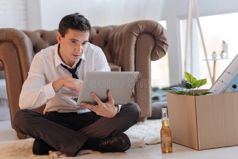 乏味人坐地板,当研究他的膝上型计算机时 库存照片