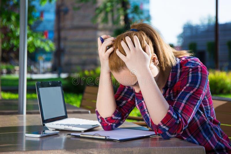 乏味十几岁的女孩与膝上型计算机一起使用在公园 库存图片