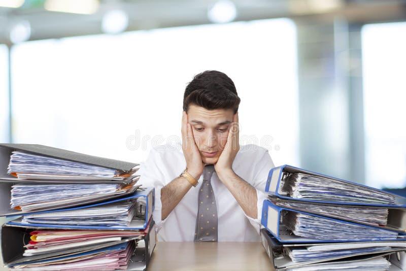 乏味商人在有文件的办公室 库存图片
