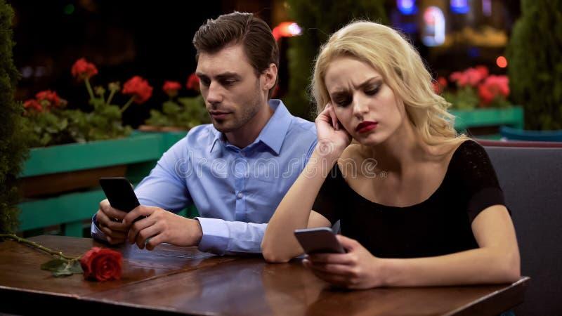 乏味在日期的两年轻人,使用智能手机,在关系的问题 图库摄影