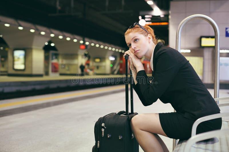 乏味女实业家等待的火车 库存照片