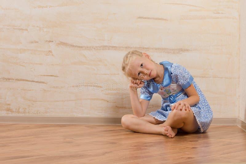 乏味小女孩坐的观看和等待 免版税库存图片