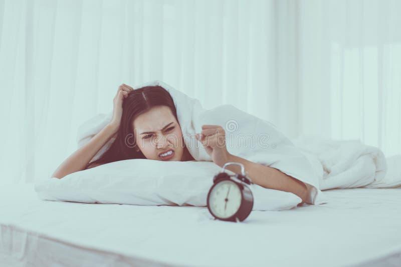 乏味年轻亚裔妇女不喜欢得到注重叫醒在床,闹钟上的早6点 免版税库存图片