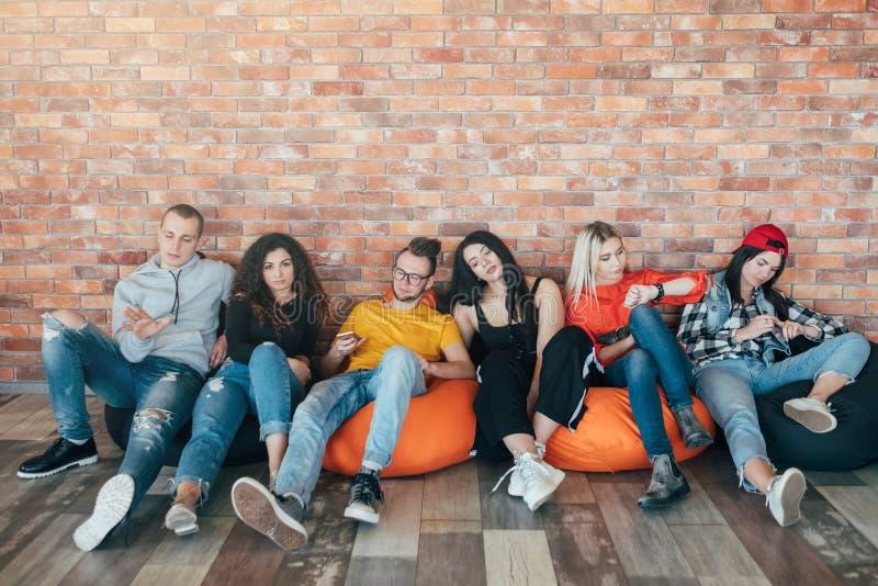 乏味的Millennials坐的休息的休息室区域 图库摄影