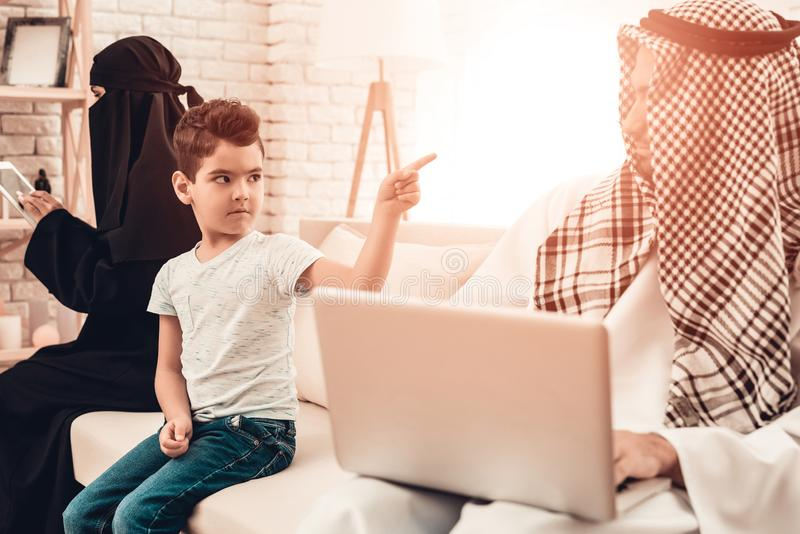 乏味阿拉伯男孩与家庭坐沙发 免版税库存照片