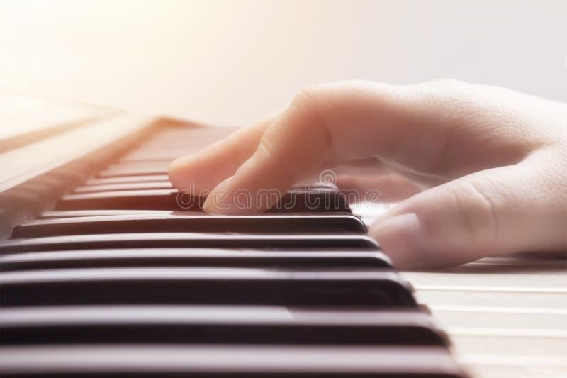 乐器背景,音乐概念 一种被弄脏的温暖的颜色定了调子白种人妇女音乐执行者手使用的照片 免版税库存图片