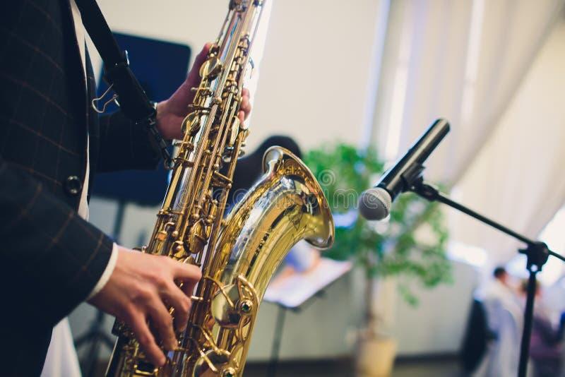 乐器,萨克管演奏员演奏爵士音乐的手萨克斯管吹奏者 女低音萨克斯管乐器特写镜头 免版税库存图片