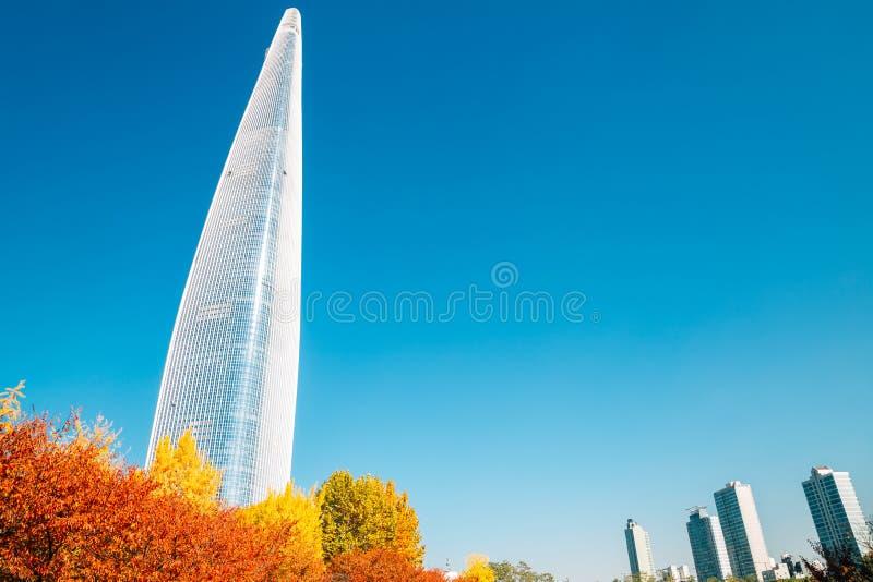 乐天世界塔和Seokchon湖有秋天槭树的在汉城,韩国 免版税库存图片