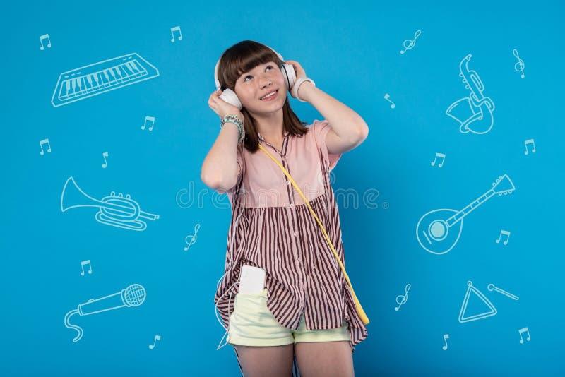 乐观女孩佩带的耳机和调查距离 免版税库存照片