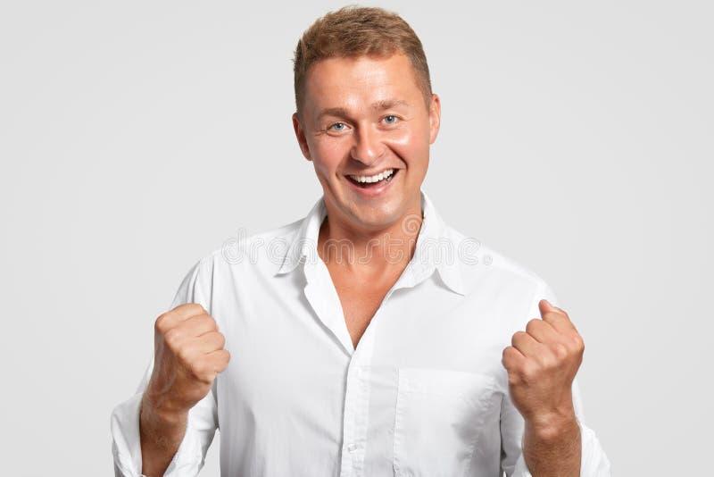 乐观快乐的欧洲男性有胜利的紧握拳头,庆祝他的成功在工作,安排友好的微笑,穿戴在丝毫 库存图片