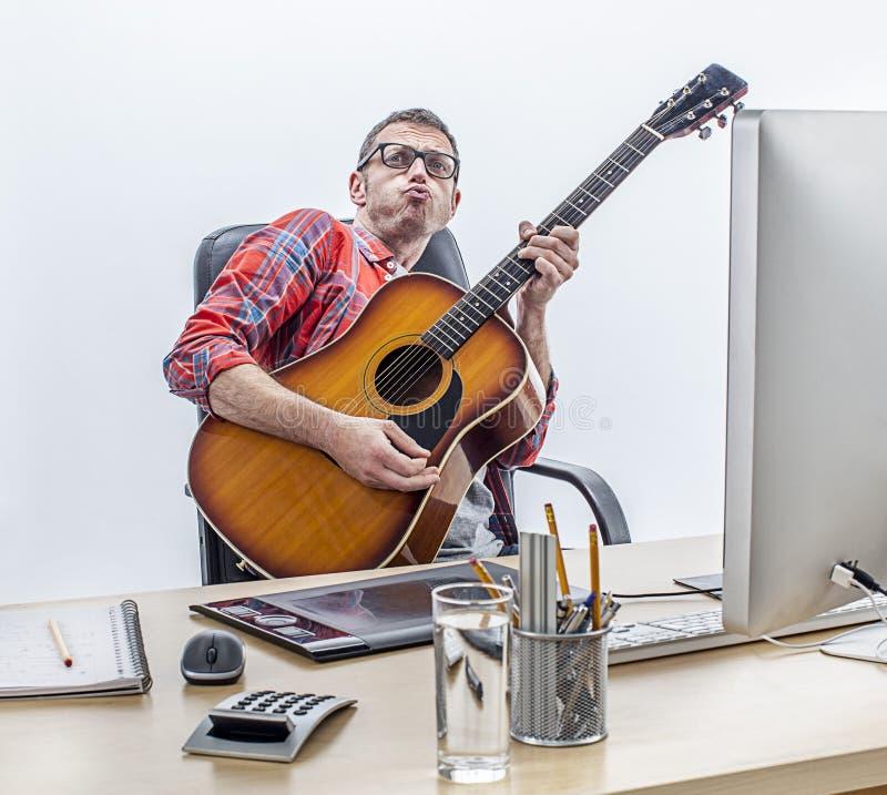 乐趣享用男性的独立弹吉他在他的计算机书桌 免版税库存图片
