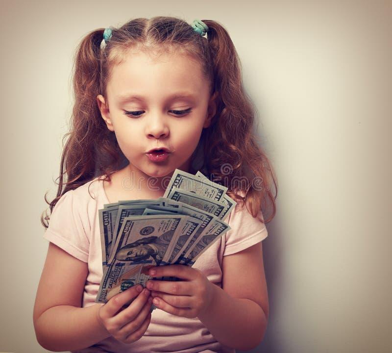 乐趣做鬼脸的孩子女孩在手上的看和计数金钱 图库摄影