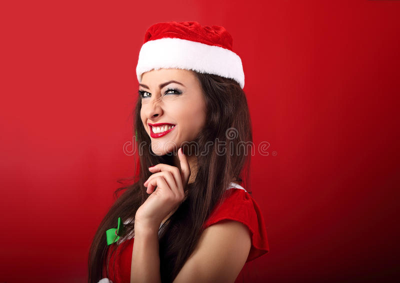 乐趣半眯着的眼睛在圣诞老人圣诞节费用激发做鬼脸的妇女 库存图片