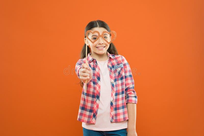 乐趣华伦泰支柱 微笑与花梢在橙色背景的党支柱的逗人喜爱的孩子 拿着心脏的滑稽的小女孩 免版税图库摄影