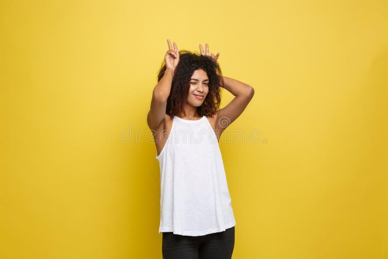 乐趣和人概念-有雀斑的微笑和显示兔子的愉快的Alfo非裔美国人的妇女特写画象  图库摄影