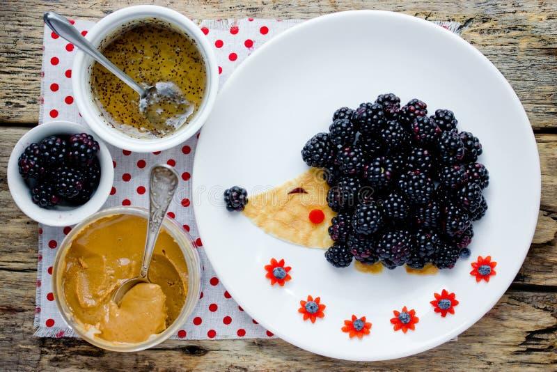 乐趣和健康早餐孩子的-可食的猬从薄煎饼与花生酱和新鲜的黑莓 库存照片