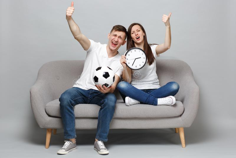 乐趣夫妇妇女人足球迷欢呼与足球的支持喜爱的队,拿着回合时钟,显示拇指 免版税库存照片
