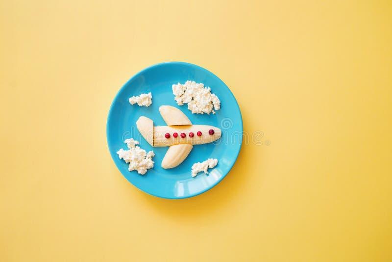 乐趣孩子的食物想法 儿童的早餐:飞机由香蕉和云彩制成由凝乳制成在一块蓝色板材 免版税图库摄影