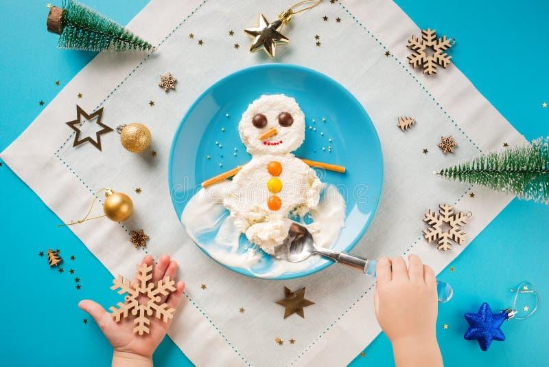 乐趣孩子的食物想法 圣诞节儿童的早餐:酸奶干酪雪人在一块蓝色板材的 匙子在儿童的手上 库存照片