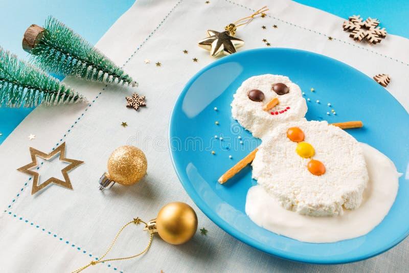 乐趣孩子的食物想法 圣诞节儿童的早餐:酸奶干酪雪人在一块蓝色板材的 免版税库存照片