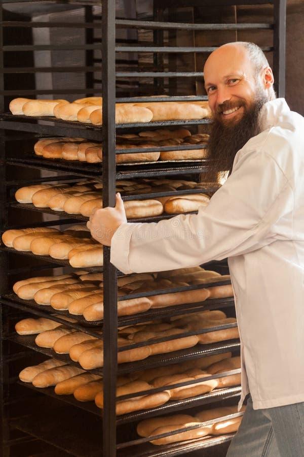 乐趣年轻成人面包师画象有长的胡子的在站立近架子的白色制服充分用新鲜的被烘烤的曲奇饼 免版税库存图片