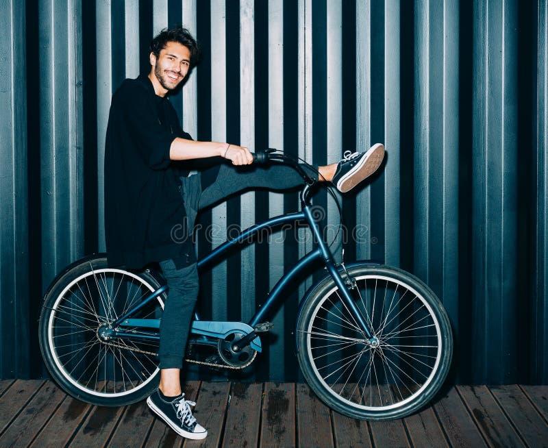 樂趣 與一個年輕人的閃光的夜畫象時興的黑成套裝備的,在葡萄酒自行車圖片
