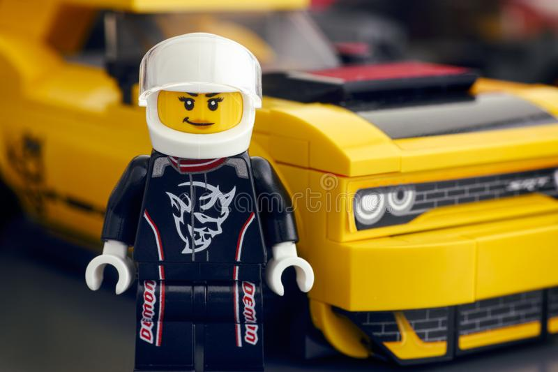 乐高2018推托挑战者SRT邪魔司机minifigure乘乐高速度冠军和他的汽车在背景 免版税库存照片
