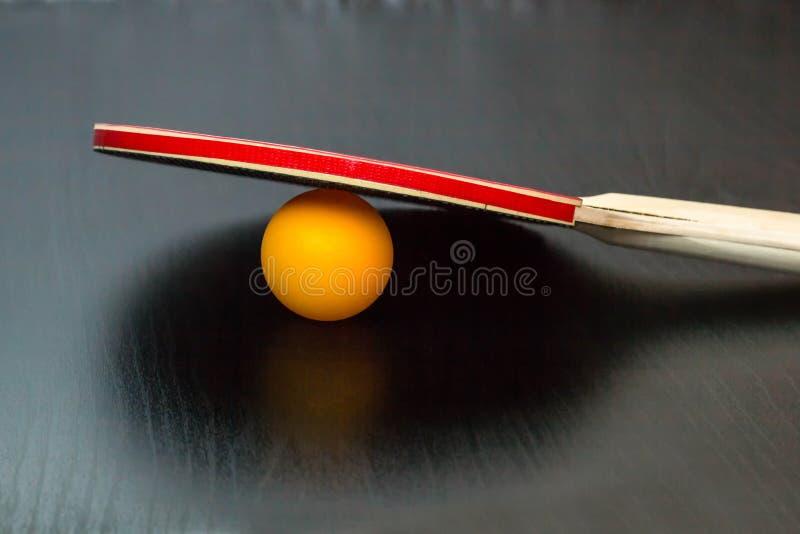 乒乓球或乒乓球球拍和球在黑背景 免版税库存图片