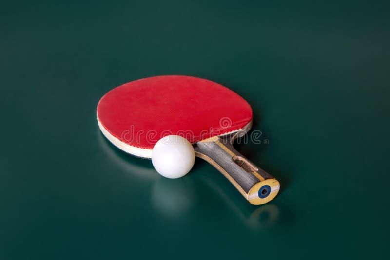乒乓球球拍和一个球在一个选材台上 免版税图库摄影