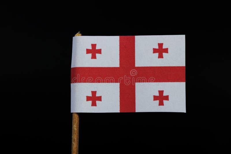 乔治亚一面国旗牙签的在黑背景 与被集中的红十字的一个白色领域在每个处所的中心 免版税库存照片