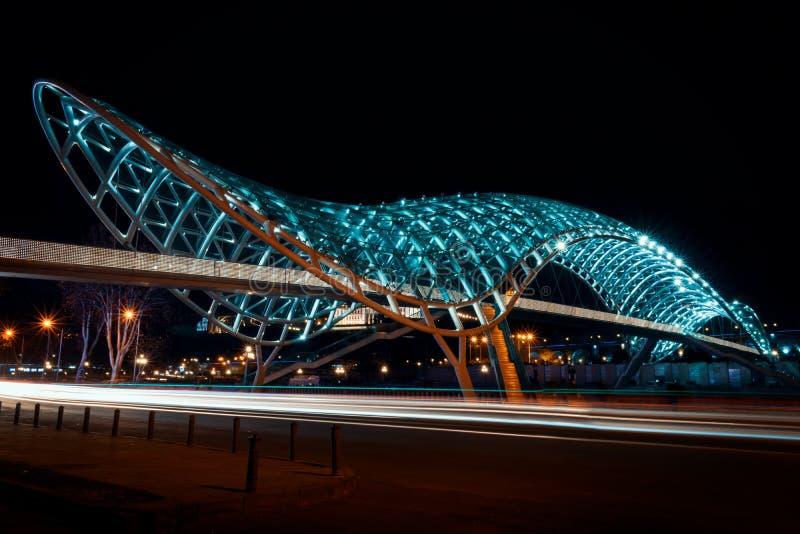 乔治亚,第比利斯- 05 02 2019年 - 在和平有启发性著名桥梁的夜视图在第比利斯市的中心 汽车光足迹- 库存图片