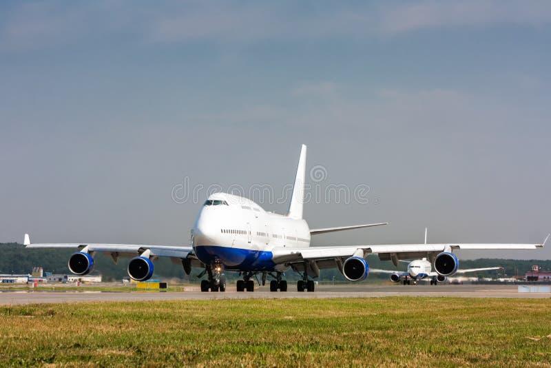 乘出租车在主要滑行道然后另一架飞机的宽身体飞机 库存照片