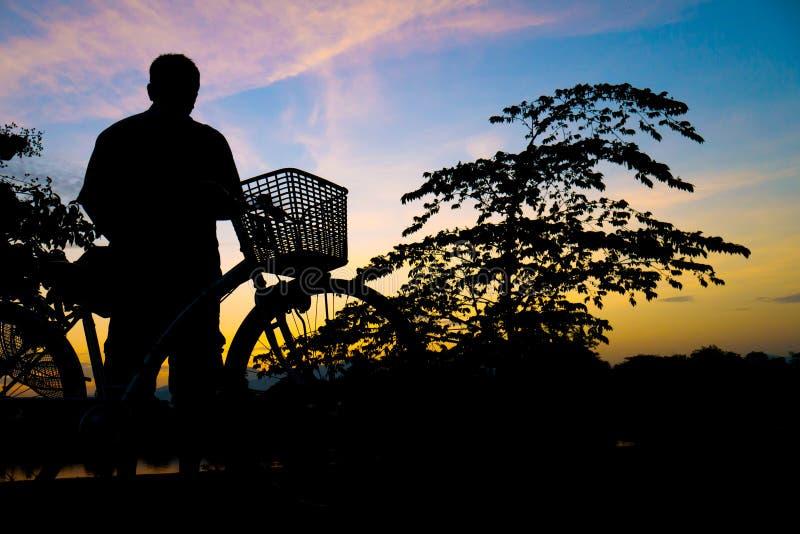 乘在暮色时间的自行车现出轮廓中年人锻炼 免版税库存照片