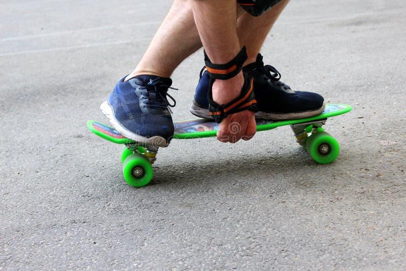 乘坐一个绿色滑板的蓝色运动鞋的一个人 免版税图库摄影