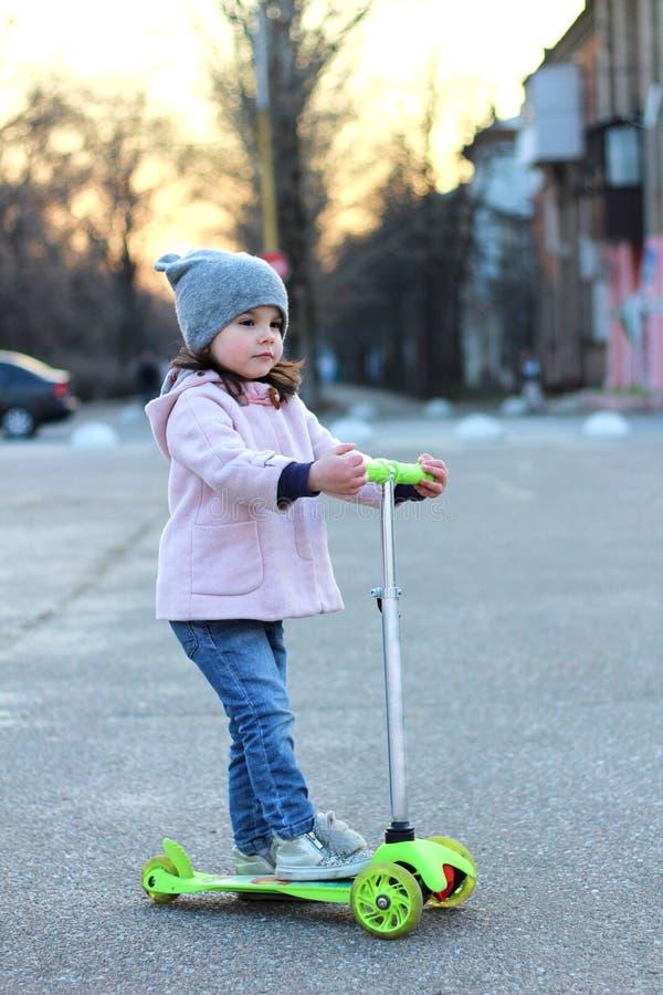 乘坐一辆单轮滑行车的帽子、外套和牛仔裤的逗人喜爱的女孩 春天城市日落 免版税库存图片