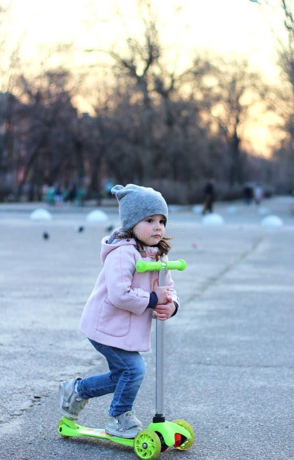 乘坐一辆单轮滑行车的帽子、外套和牛仔裤的逗人喜爱的女孩 春天城市日落 库存图片