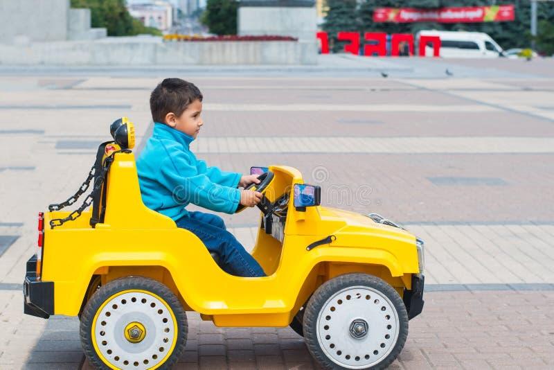 乘坐一辆汽车的男孩在公园 免版税库存照片