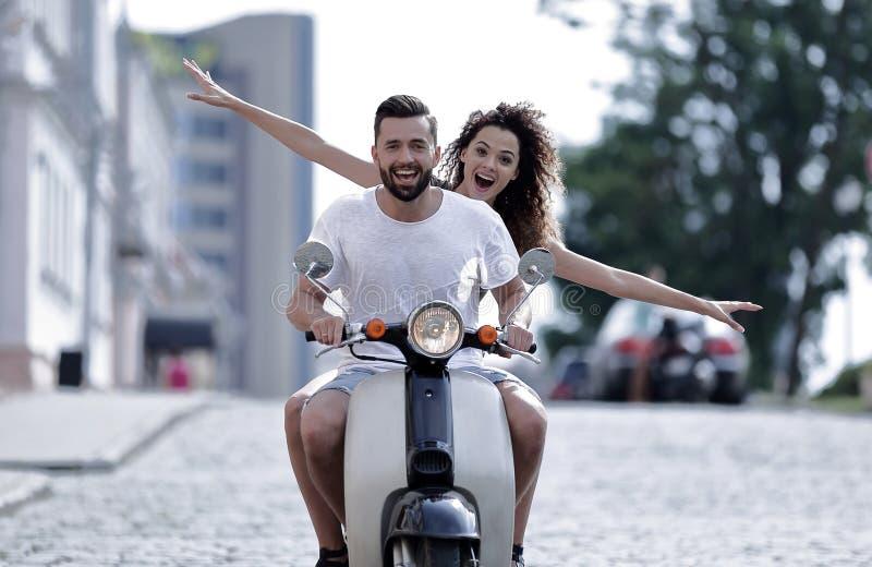 乘坐一辆滑行车的愉快的年轻夫妇在城市在一个晴天 库存图片