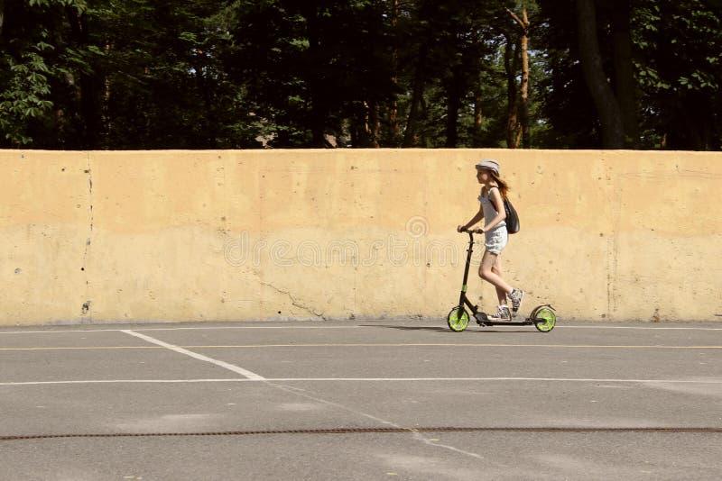 乘坐一辆滑行车的逗人喜爱的女孩在公园 免版税库存图片