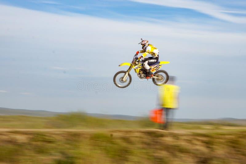 乘坐一辆黄色摩托车的红色盔甲的人在秋天轨道 免版税库存图片