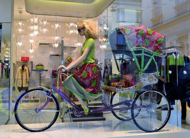 乘坐三轮车人力车的一名金发妇女的美丽的时装模特 免版税库存图片