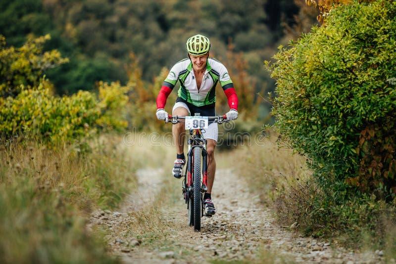 乘坐上升在与微笑的一个山行迹的男性车手骑自行车者在面孔 免版税库存图片